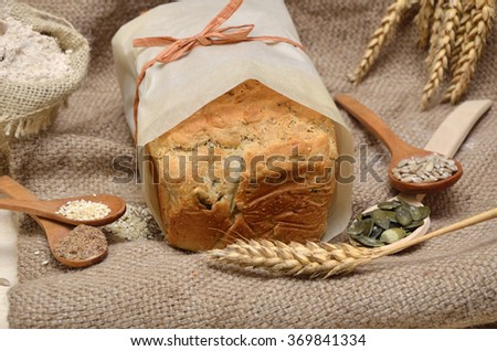 Tasty homemade whole grain bread with healthy seeds and pumpkin, flax, sunflower and sesame seeds in wooden spoons - stock photo
