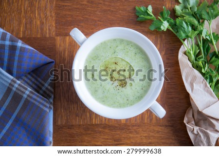 Tasty hot cream of broccoli with olive oil and parsley - stock photo