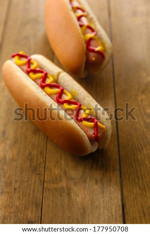 Tasty hot dogs on wooden table - stock photo