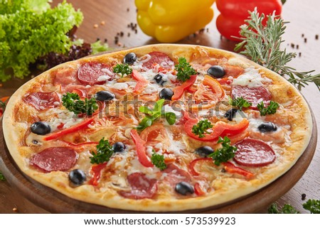 Tasty hot pizza with salami and pepper