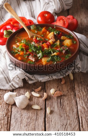 Tasty Hungarian goulash soup bograch close-up on the table and ingredients. vertical