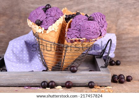 Tasty ice cream with berries in waffle cones on brown wooden background - stock photo