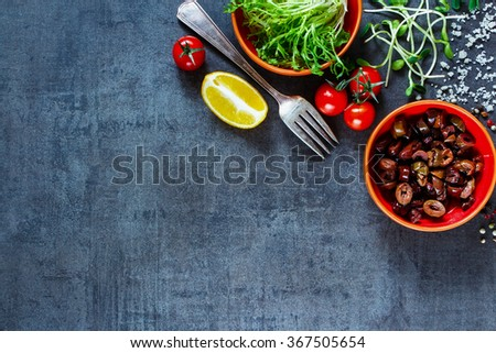 Tasty ingredients for cooking (tomatoes, lemon, salad leaves, olives and spices) on dark old background. Vegetarian food, health or cooking concept. Background layout with free text space. Top view. - stock photo