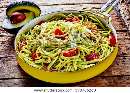 Tasty Italian fettuccine pasta cooked with avocado pear, fresh tomato and pine nuts garnished with grated parmesan and serving in a rustic frying pan on an old wooden table - stock photo