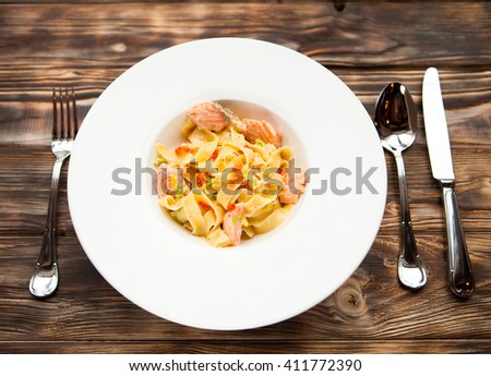 Tasty Italian Pasta fettuccine with salmon and caviar on a white dish on a wooden background. Top view. - stock photo
