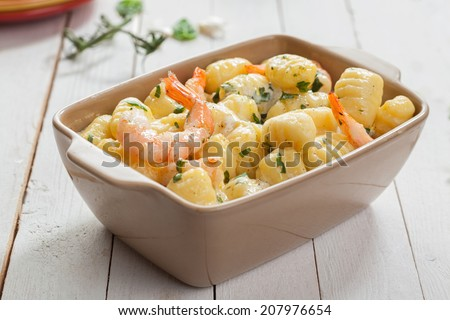 Tasty Italian seafood cuisine with grilled pink prawns in gnocchi pasta, or semolina dumplings, served in a casserole seasoned with fresh herbs