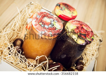 Tasty jam in the glass jars with chestnuts in hay. Seasonal food theme. Still life. - stock photo