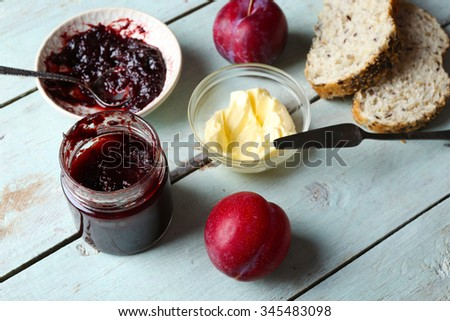 Tasty jam in the jar and bowl, butter, fresh bread and plums on blue wooden background - stock photo
