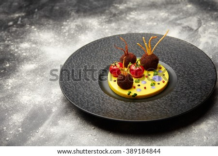 Tasty juicy fried meatballs with tomato on a potatoes in a black plate. Shallow depth of field - stock photo