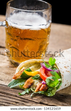 Tasty kebabs and cold beer on old wooden table