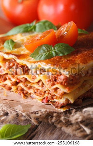 Tasty lasagna with basil and tomatoes on an old table, vertical close-up