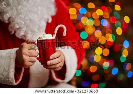 Tasty latte with whipped cream and candy cane in Santa hands - stock photo