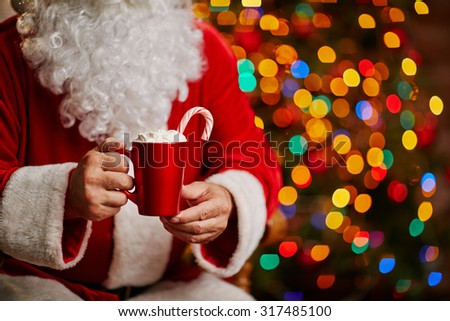 Tasty latte with whipped cream held by Santa - stock photo