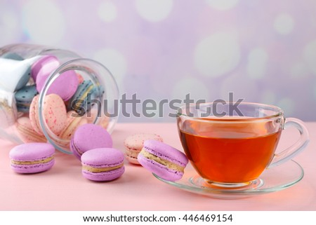 Tasty macaroons with tea on table