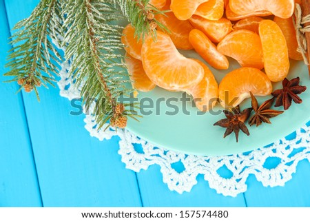 Tasty mandarine's slices on color plate on blue background - stock photo