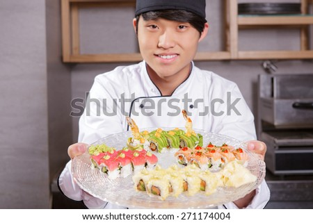 Tasty meal for big company. Young and smiling Asian cook in white uniform stretching out a big plate with various kinds of sushi rolls on it - stock photo