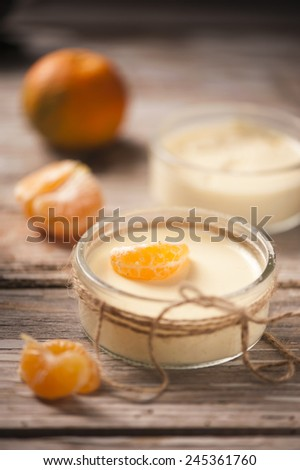 Tasty milk dessert with fresh tangerine pieces in glass bowl, on wooden background  - stock photo