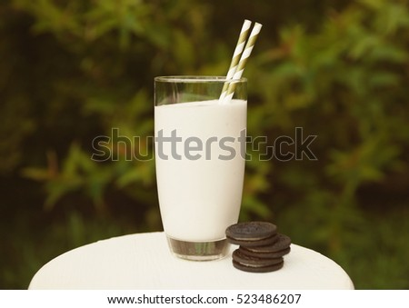 Tasty milk shake with cookies on table, outdoor
