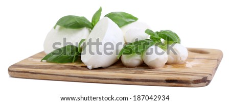 Tasty mozzarella with basil on wooden board isolated on white - stock photo