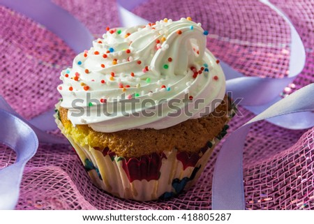 Tasty muffin cake with protein cream, decorated with colorful confectionary sprinkles