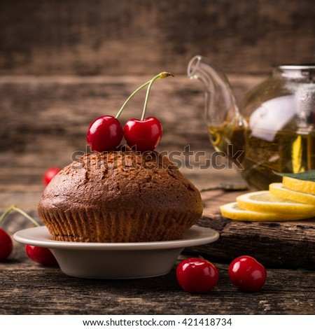 Tasty muffin with cherry and mint on vintage wooden background - stock photo