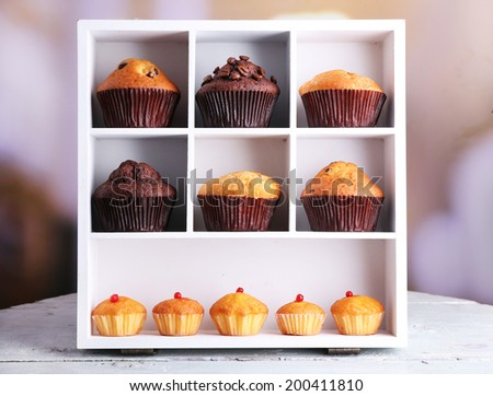 Tasty muffins on wooden shelves, on bright background - stock photo