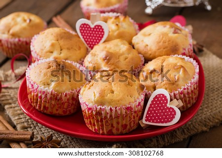 Tasty muffins with apple and cinnamon on a wooden background