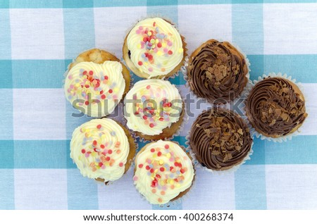 Tasty muffins with vanilla and chocolate cream decorated with sugar candy - stock photo