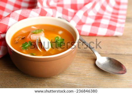 Tasty mussel soup with shrimps in bowl on wooden background - stock photo
