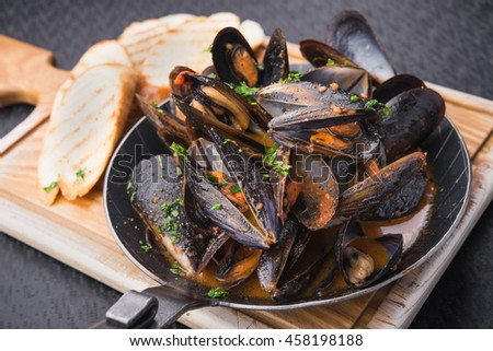 tasty mussels in pan on black table - stock photo