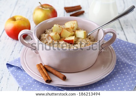 Tasty oatmeal with apples and cinnamon on wooden table - stock photo