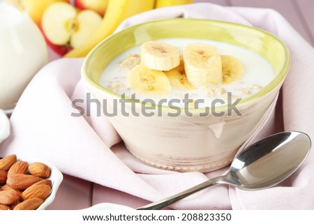 Tasty oatmeal with bananas and milk on table close up - stock photo