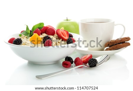 tasty oatmeal with berries and cup of tea, isolated on white - stock photo