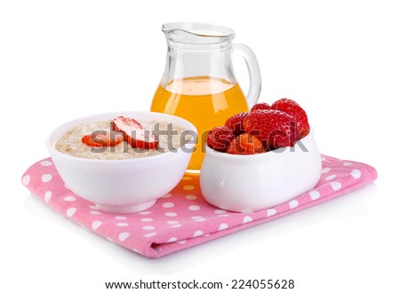 Tasty oatmeal with berries and juice isolated on white - stock photo