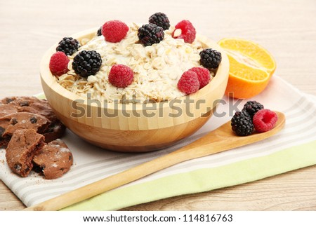 tasty oatmeal with berries, on wooden table