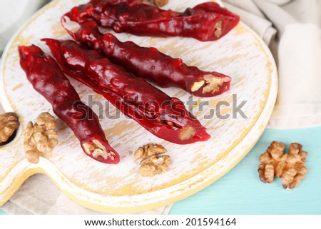 Tasty oriental sweets (churchkhela) and fresh nuts on cutting board, on wooden background - stock photo