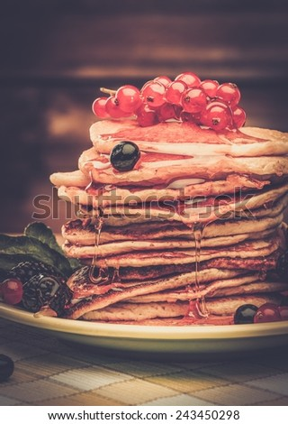 Tasty pancakes with maple syrup and fresh berries on a plate  - stock photo