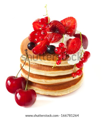 Tasty pancakes with whipped cream and berries on a white.
