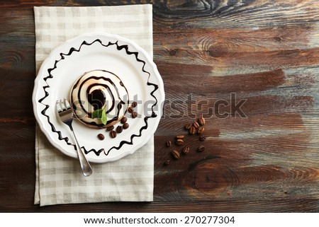 Tasty panna cotta dessert on plate, on wooden table - stock photo