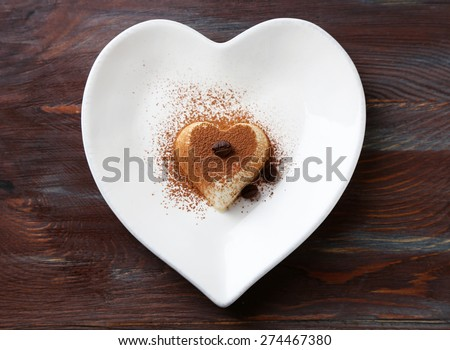Tasty panna cotta dessert on plate, on wooden table - stock photo