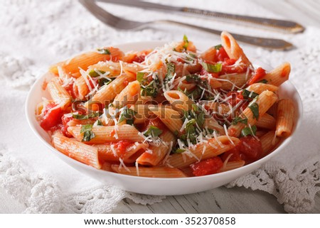 Tasty pasta arrabbiata with parmesan closeup on a plate on the table. horizontal