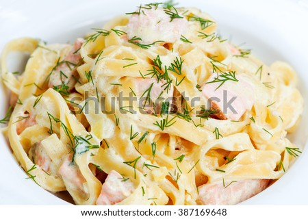 tasty pasta with salmon, dill on plate - stock photo