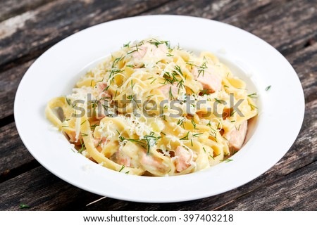 tasty pasta with salmon, dill on plate. - stock photo