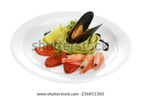 Tasty pasta with shrimps, mussels and tomatoes isolated on white - stock photo