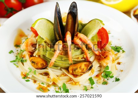 Tasty pasta with shrimps, mussels, tomatoes on plate close-up - stock photo