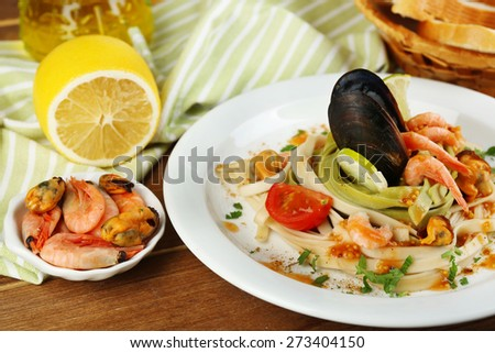 Tasty pasta with shrimps, mussels, tomatoes on plate on wooden background - stock photo