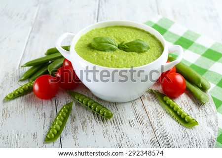 Tasty peas soup and cherry tomatoes on table close up - stock photo