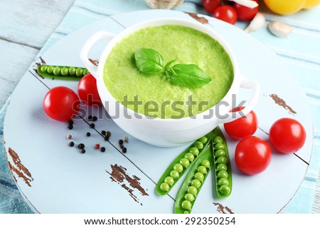Tasty peas soup and vegetables on table close up - stock photo