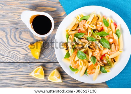 tasty penne pasta salad with shrimps, mussels and baby spinach leaves on a white dish, caramelized balsamic vinegar in a sauce boat and lemon slices on an rustic table, top view - stock photo