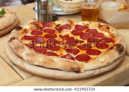 Tasty pepperoni pizza on a wood background - stock photo